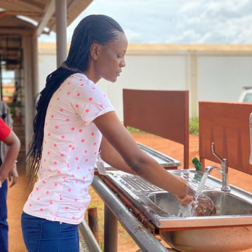 A contract employee washing her hands with soap and running water as part of coronavirus prevention efforts.