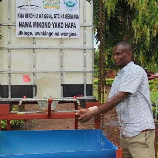 An official from Geita Town Council testing the public hand washing facilities donated by Geita Gold Mine.