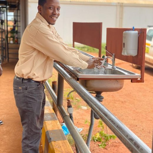 A Geita Gold Mine employee practicing good hygiene by washing his hands with soap and water at the entrance of the mine.