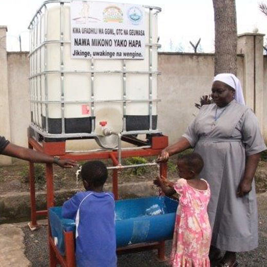 Sr. Adelberra Mukure (right), Director for Moyo wa Huruma Orphanage Centre demonstrating to the children how to use the hand washing facility.