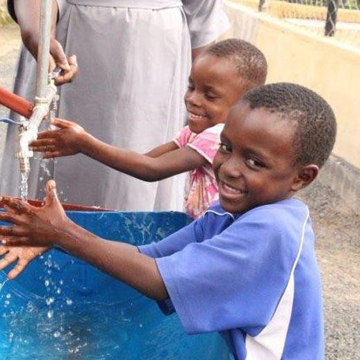 Children at Moyo wa Huruma Orphanage Center washing their hands at a facility donated by Geita Gold Mine.